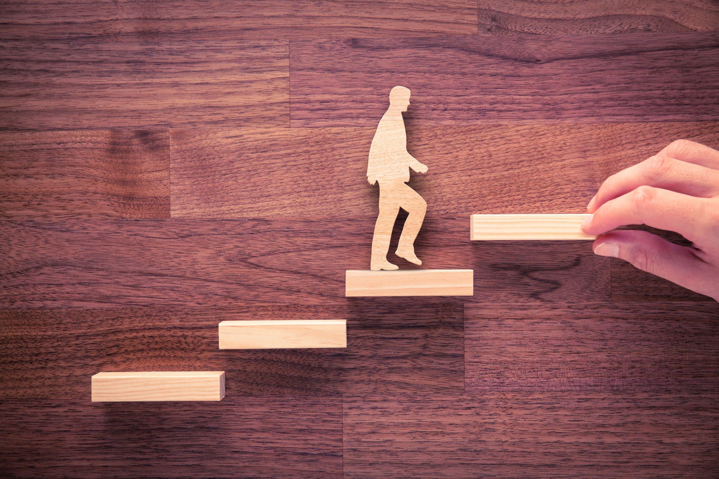 Peças de madeira clara colocadas em cima de uma mesa representando um homem subindo degraus de escadas.