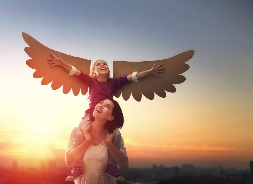 Mulher branca e jovem sorridente, com sua filha nos ombros. A criança esta com asas de papelão nos braços, brincando de ser um pássaro. Ao fundo há uma paisagem urbana com o pôr do sol alaranjado.
