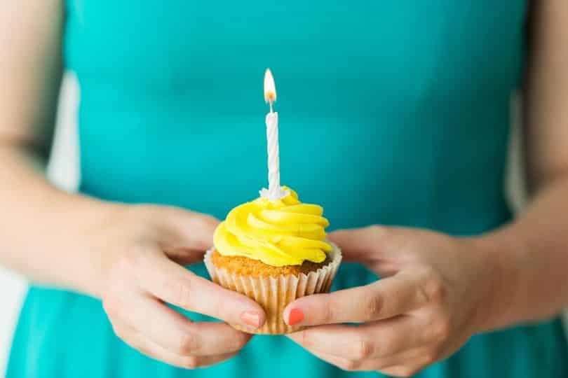 Mulher segura cupcake de cobertura amarela com uma vela acesa.