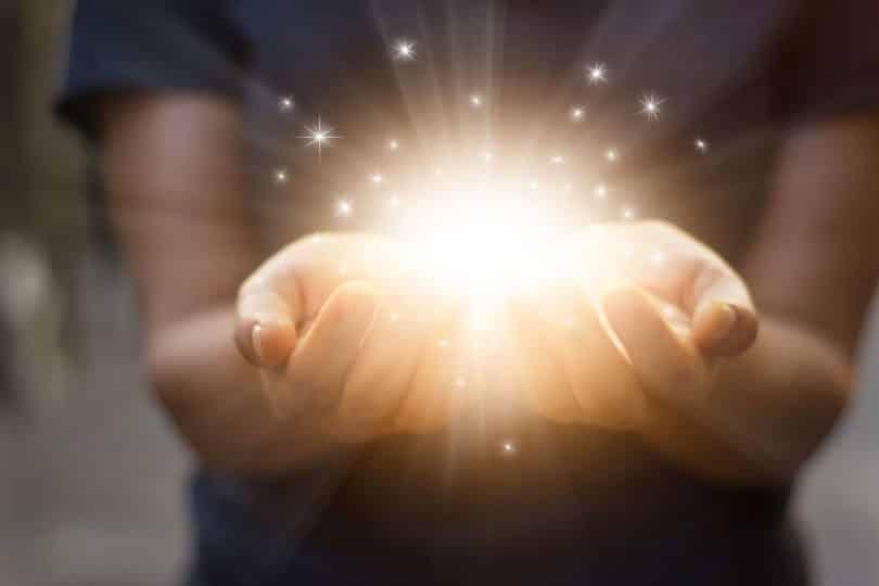 Mãos de mulher com luz em seu interior.