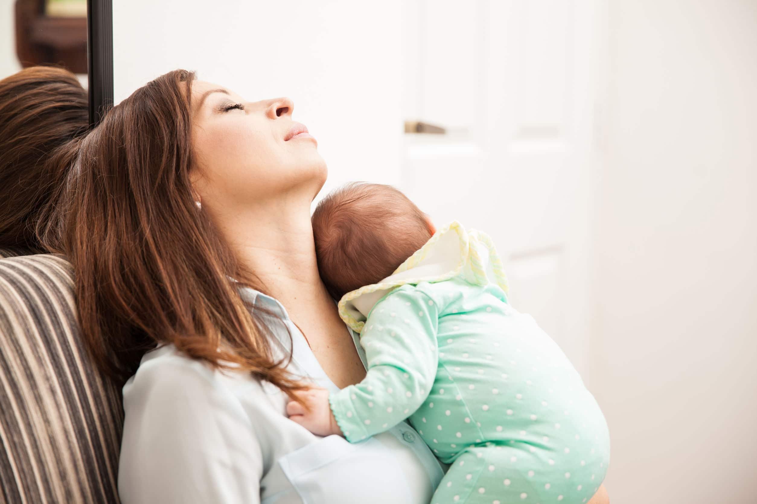 Mulher branca jovem sentada em uma poltrona demonstrando cansaço enquanto segura um bebê recém nascido.