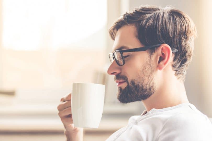 Homem sorrindo e segurando uma xícara de café.