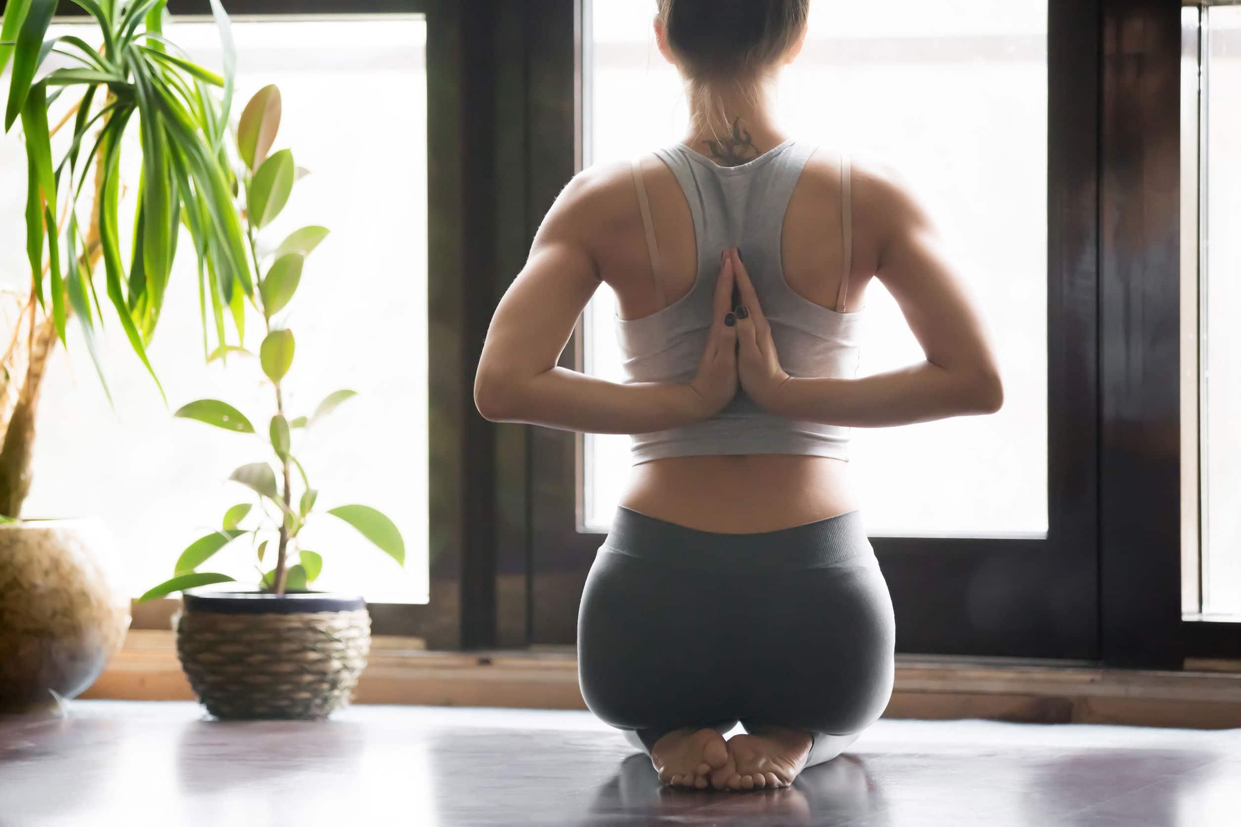 Mulher praticando yoga e meditação na sala de casa. Um planta ao lado da mulher e uma janela à frente. Bastante claridade entrando pela janela.