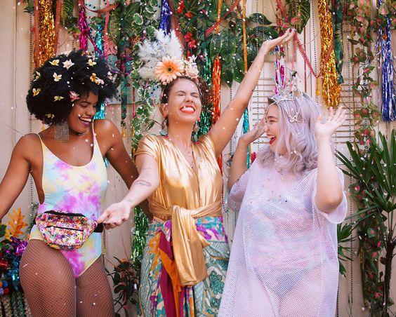Três garotas pulando carnaval fantasiadas e cheias de glitter. Uma negra e duas brancas.