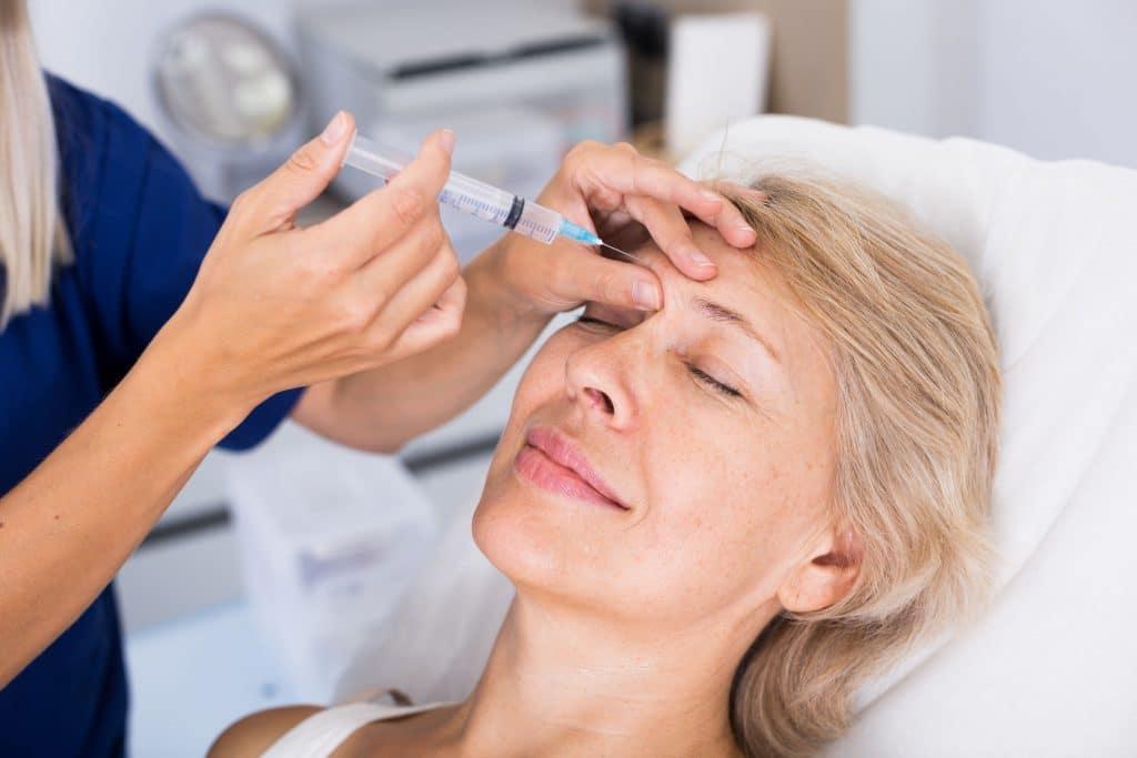 Mulher branca, mais velha, em um consultório de estética, recebendo injeções de botox na testa.