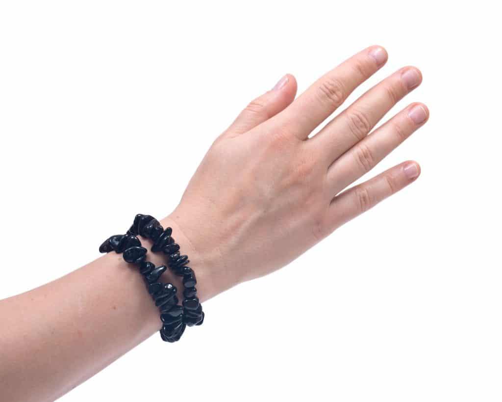 Braço de pessoa branca, em um fundo branco, usando uma pulseira de pedras de turmalina negra.