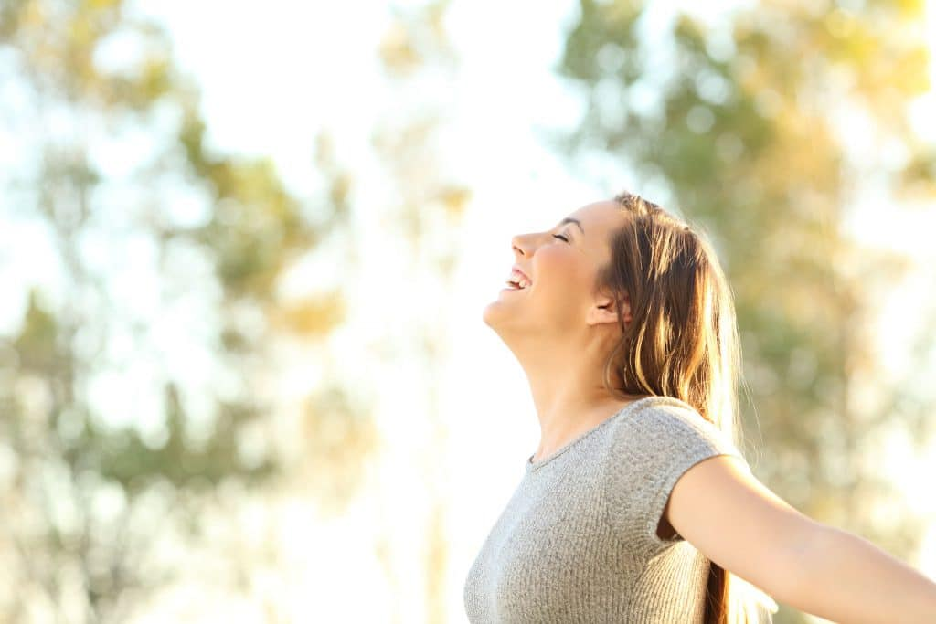 Visão do lado de uma mulher olhando para o céu. Fundo de natureza.