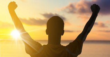 Silhueta de homem com os braços erguidos. Fundo de pôr-do-sol.