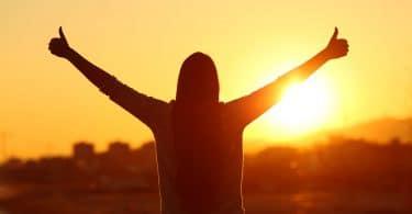 Mulher com os braços levantados fazendo um sinal de jóia. Fundo de pôr-do-sol.