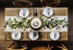 Mesa pratos postos e bolo no meio. Decoração de folhas e flores.