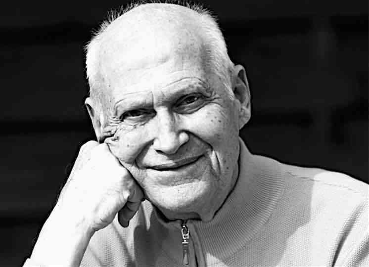 Um senhor branco que está sorrindo enquanto apoia o rosto nas mãos. Ele é Bert Hellinger o criador da metodologia.