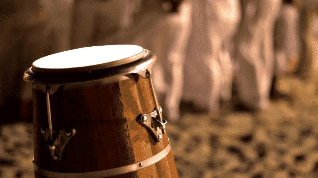 Foto de um atabaque com um grupo de umbanda atrás