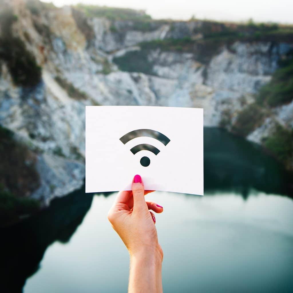 Mulher segurando um papel cortado no formato do um sinal de Wi-fi. Fundo de lago e montanhas. Pode ser entendido como estar conectado com a natureza e o universo.