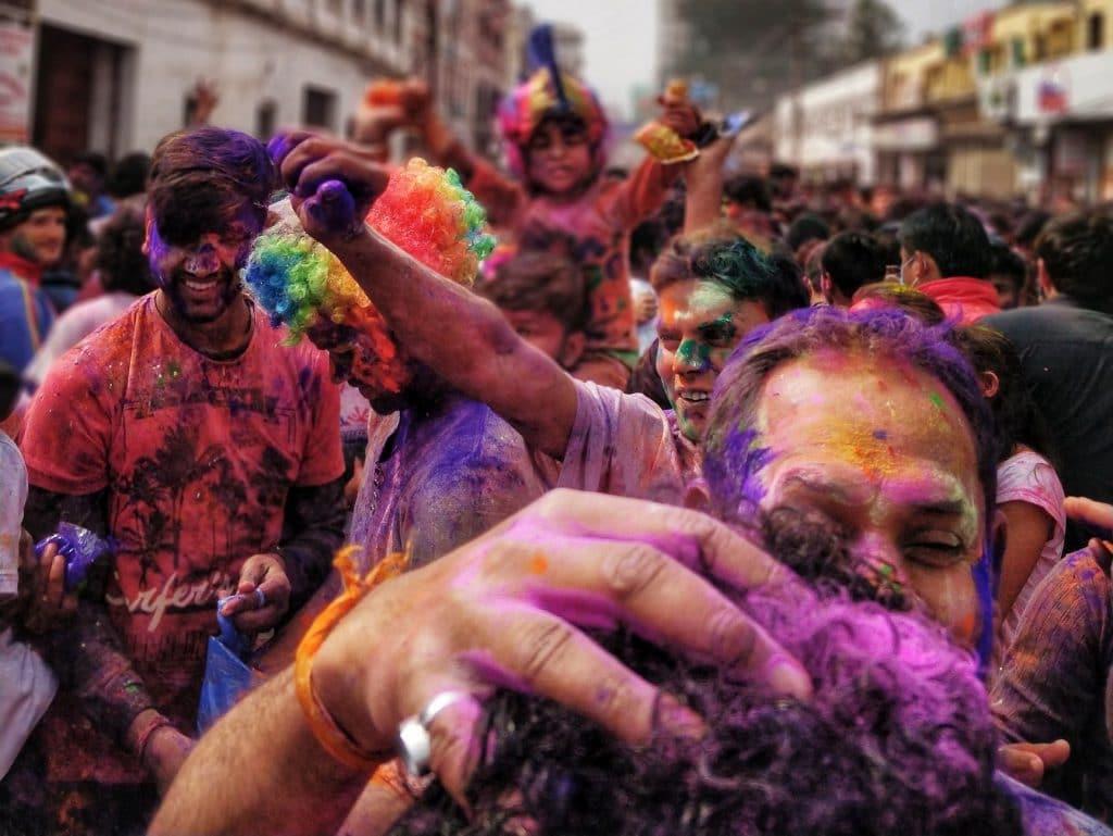 Folia na rua. Fumaça colorida e pessoas pintadas. Transmite sentimento de alegria.