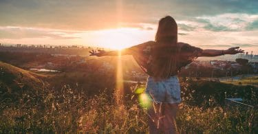 Menina em montanha com os braços abertos. Fundo de pôr-do-sol.