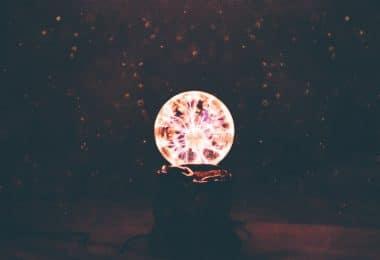 Bola de plasma multicolorido em quarto de luz fraca.