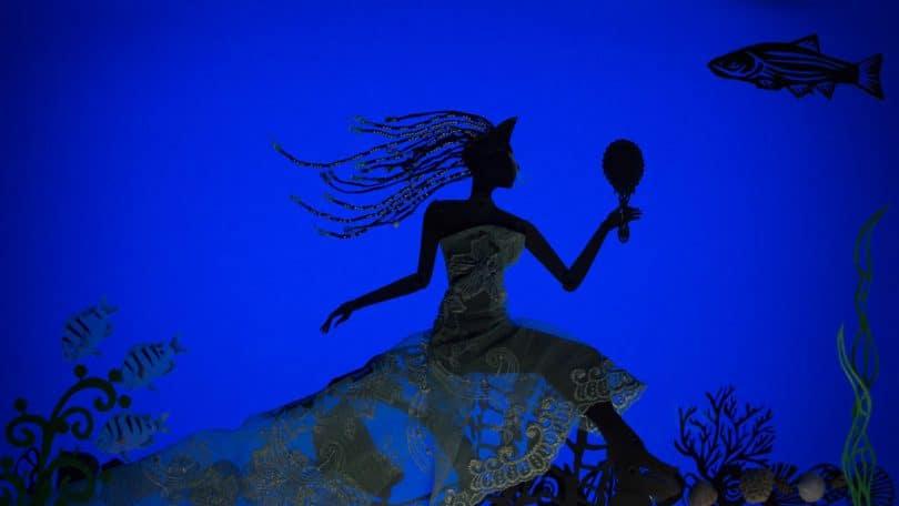 Silhueta de uma mulher segurando um espelho representando Iemanjá.