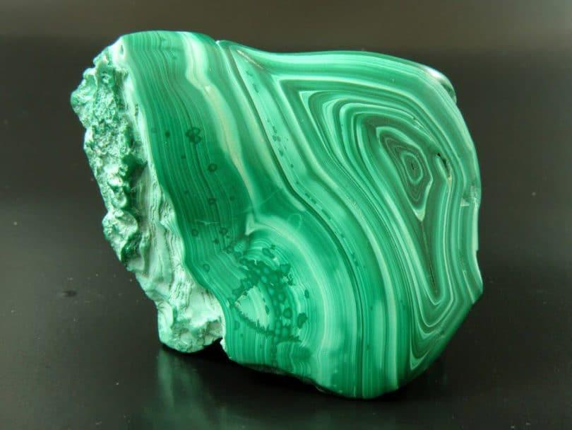 Pedra malaquita. Pedra com tons de verde e preto. Contém um padrão de desenhos circulares. Fundo preto.