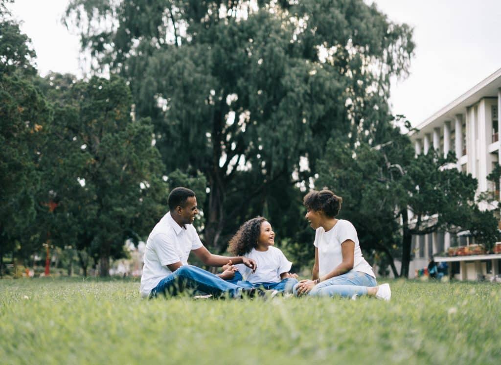 Mãe e pai sentados em um gramado ao lado de sua filha