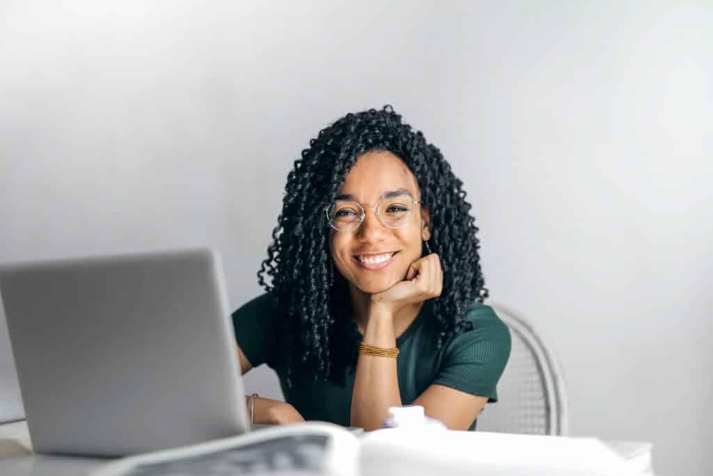 Mulher sorrindo em frente ao seu laptop.