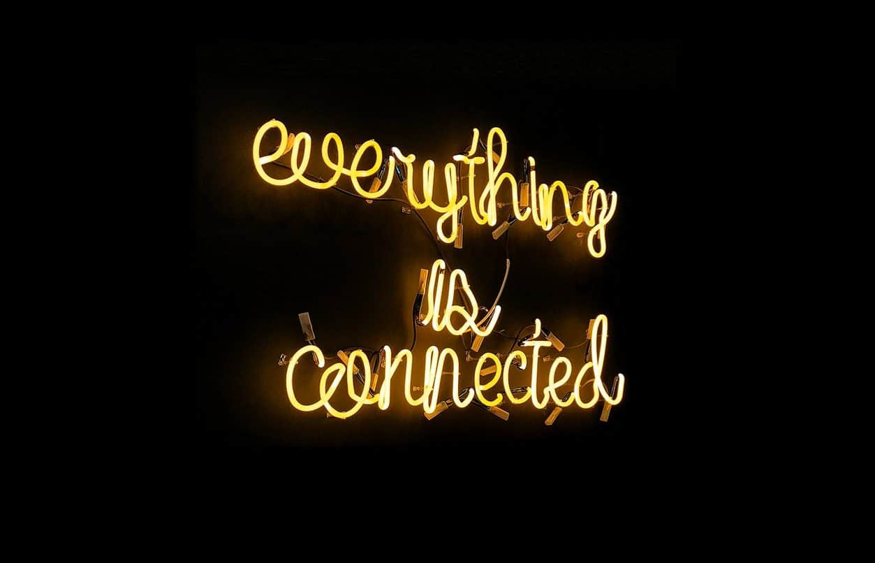 "Letras em neon amarelo com frase ""everything is connected"". Fundo preto."