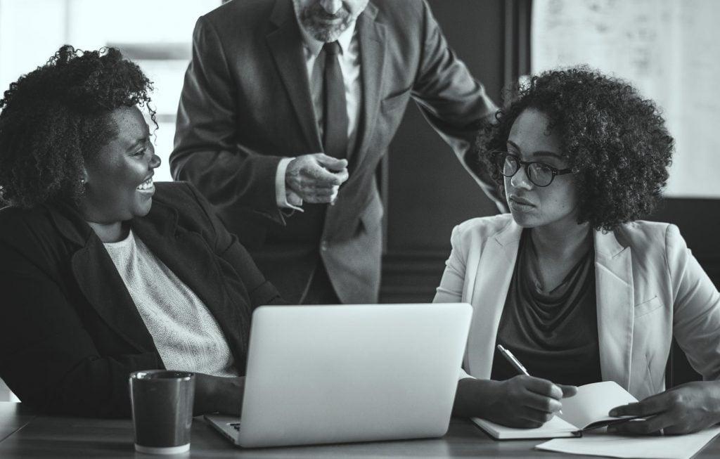 Duas mulheres negras, vestindo roupas sociais, sorridentes e trabalhando em um computador enquanto um homem está atrás delas comentando algo.