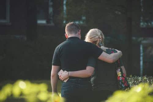 Imagem distante de duas pessoas de costas, homem e mulher, abraçados, vestidos de preto e caminhando.