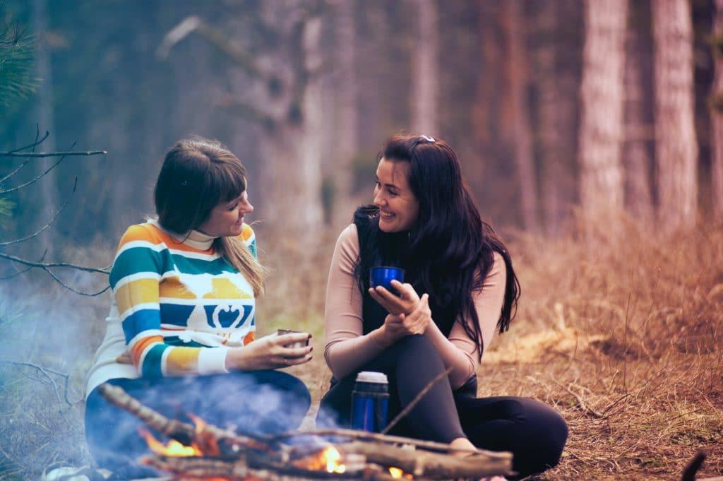 Duas mulheres sentadas em uma floresta, em frente a uma fogueira, conversando.