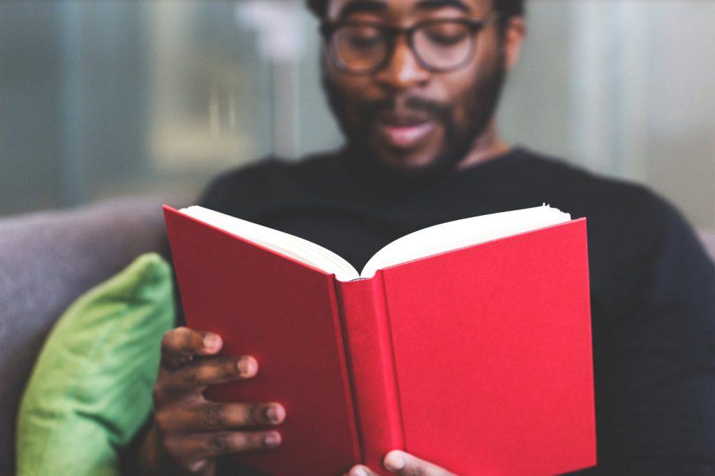 Homem sentado lendo um livro.