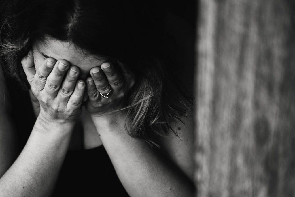 Foto preta e branca de mulher chorando apoiando o rosto nas mãos.