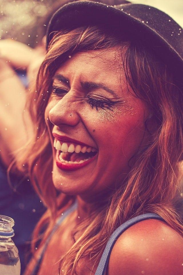 Mulher aproveitando o carnaval. Está pintada e com glitter no rosto. Usa um chapéu preto.