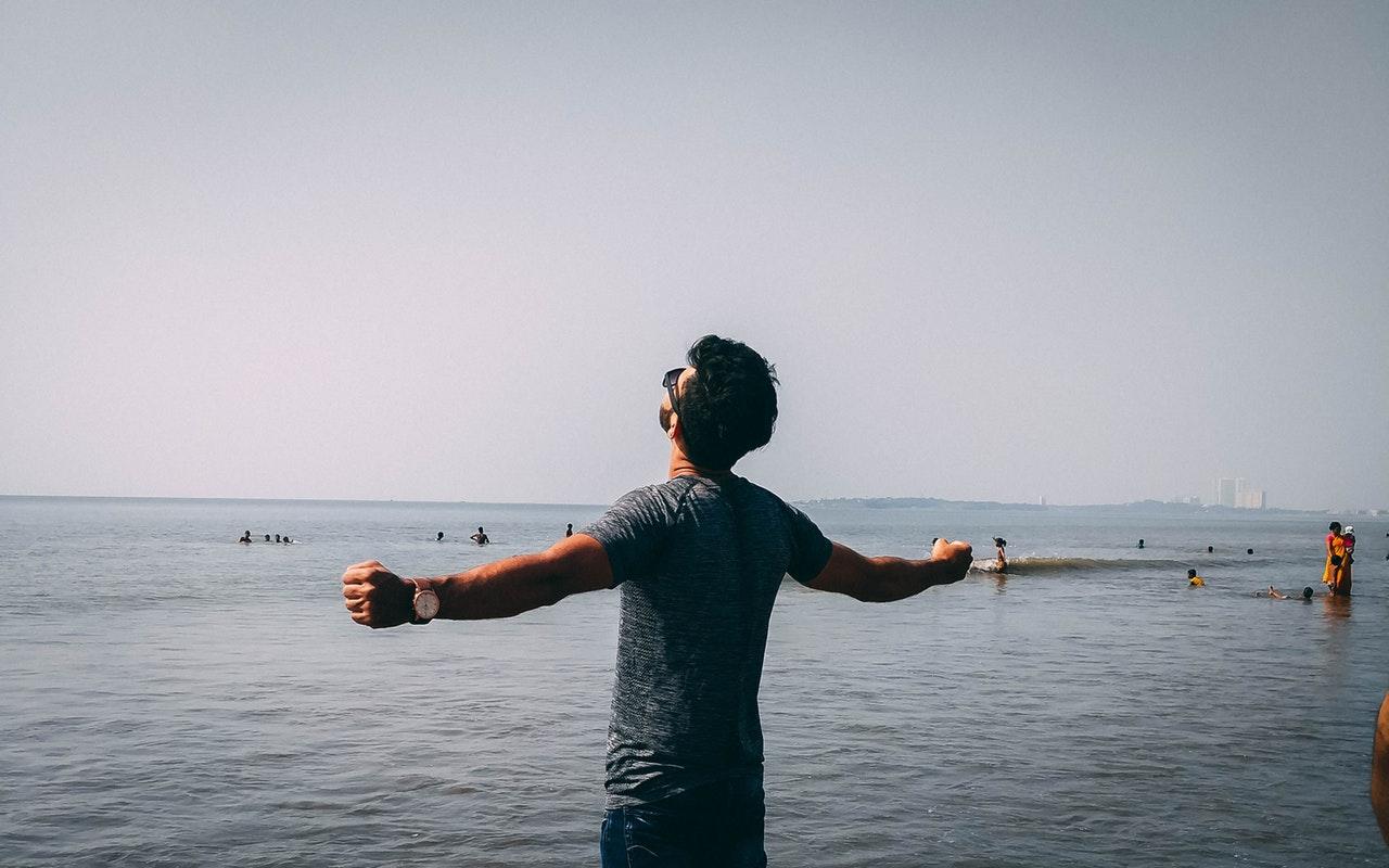 Homem na praia com os braços abertos em sinal de conquista, aproveitamento.