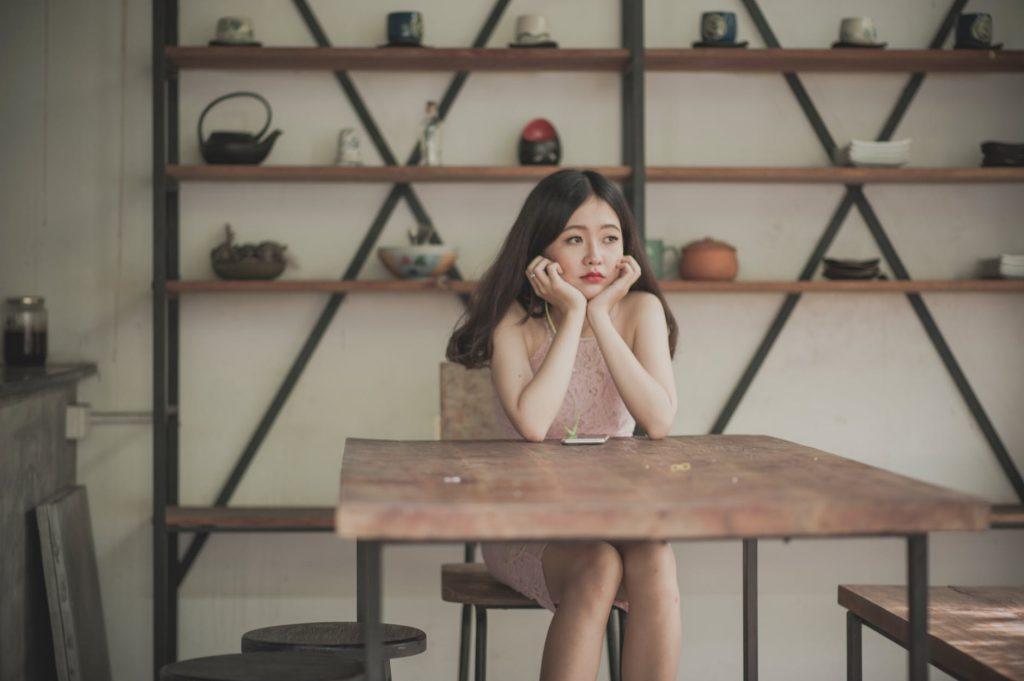 Mulher com feição de tristeza sentada em uma mesa apoiando a cabeça.