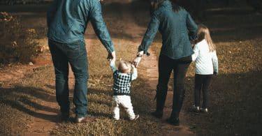 Mãe e pai segurando crianças pelas mãos