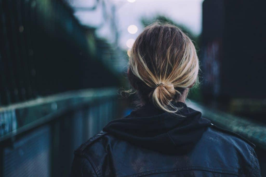 Mulher de costas olhando para uma estrada.