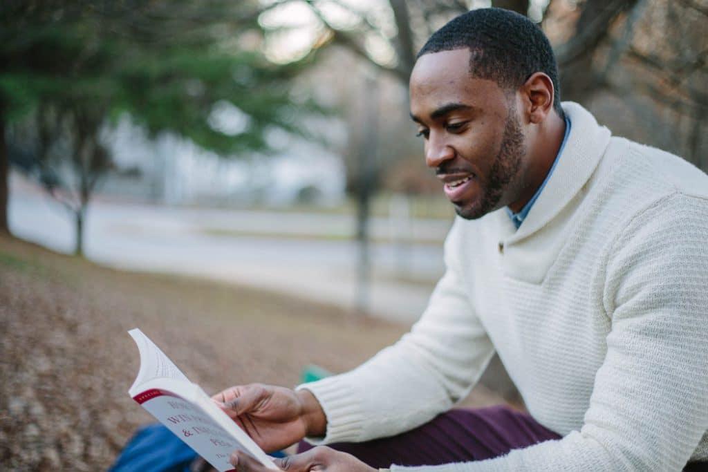 Homem lendo sentado em um parque.