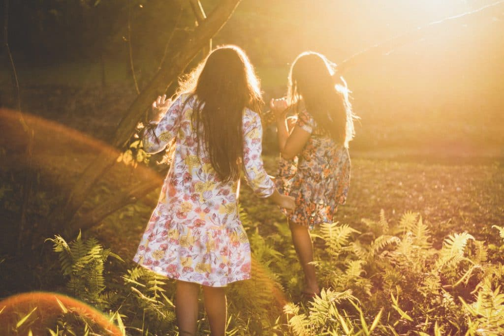 Meninas brincando em uma floresta.