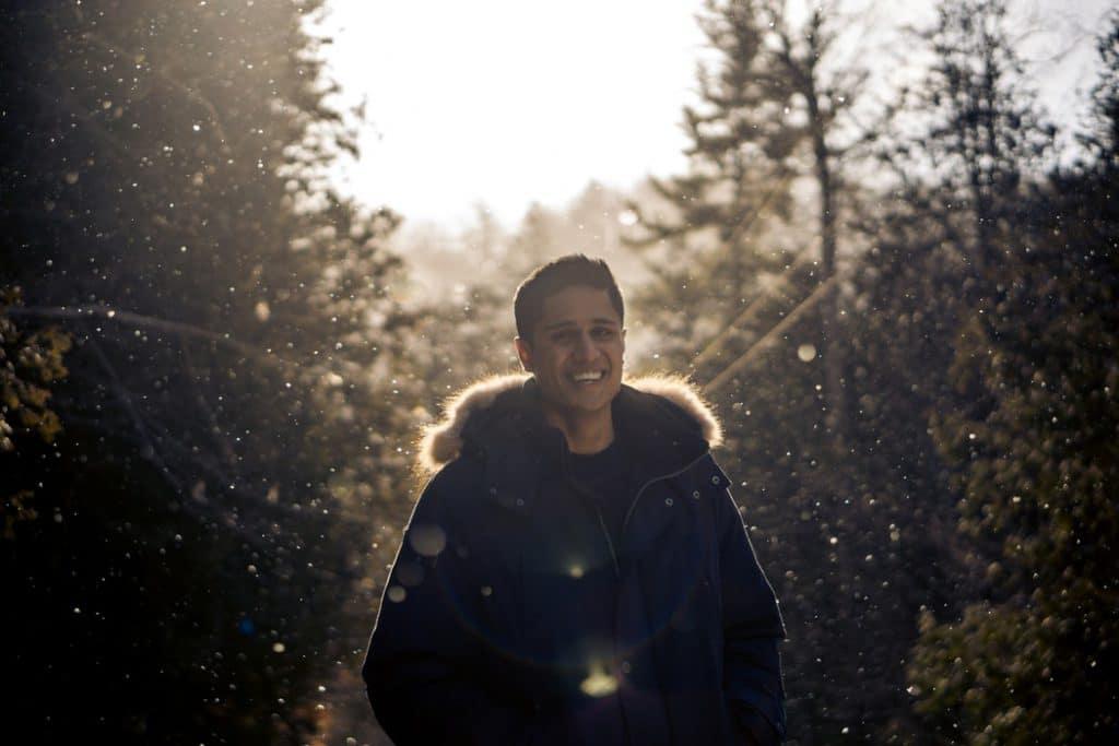 Homem sorrindo. Ele está em uma floresta iluminada pelo sol ao fim de tarde.