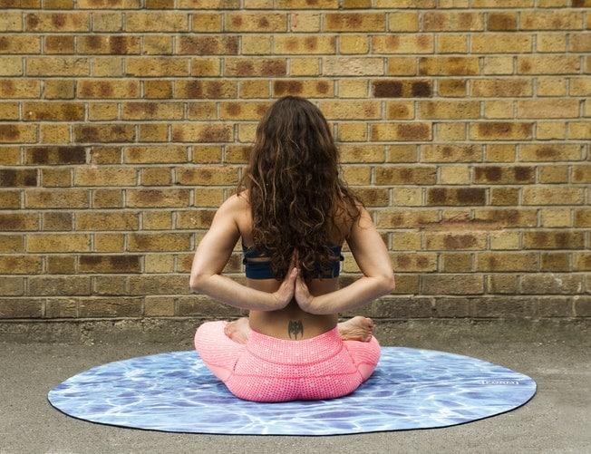 Mulher sentada em um tapete de yoga azul.