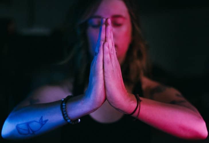 Mulher com as mãos em forma de Namastê.