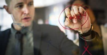 Homem vestido de social, escrevendo com canetão vermelho em uma lousa de vidro.