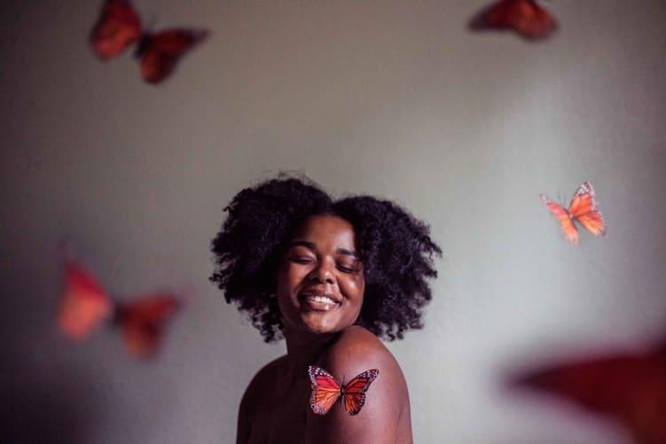 Mulher negra sorrindo com borboletas voando ao redor dela.