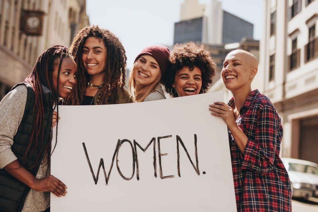 Várias mulheres, de diversas etnias, segurando um cartaz branco escrito a palavra mulher em preto.