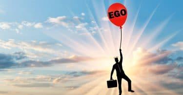 """Homem carregando mala e usando uma coroa enquanto segura um balão vermelho com a a palavra """"ego"""" desenhada."""
