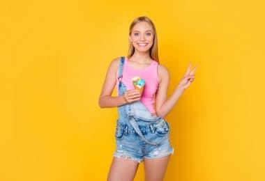 Menina segurando um sorvete de cone e fazendo o sinal da paz com a outra mão.