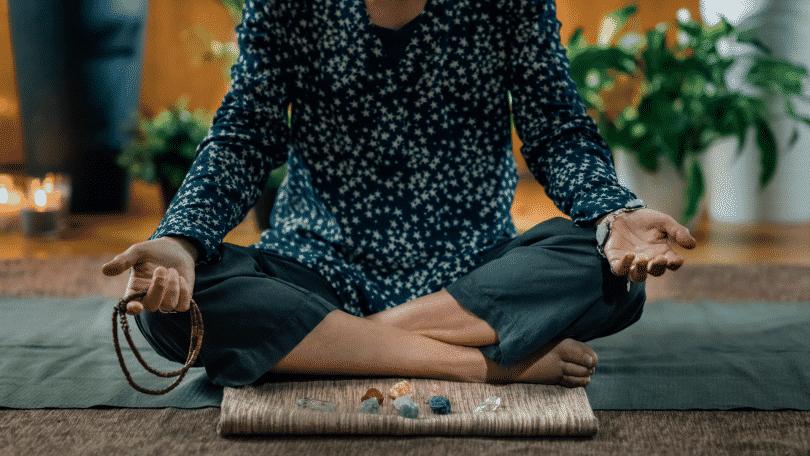 Mulher meditando com pedras de energia positiva