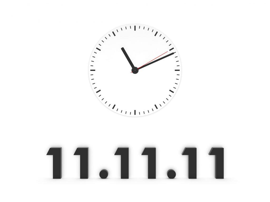 Ilustração em preto e branco de um relógio analógico redondo, logo abaixo há escrito os números 11.11.11