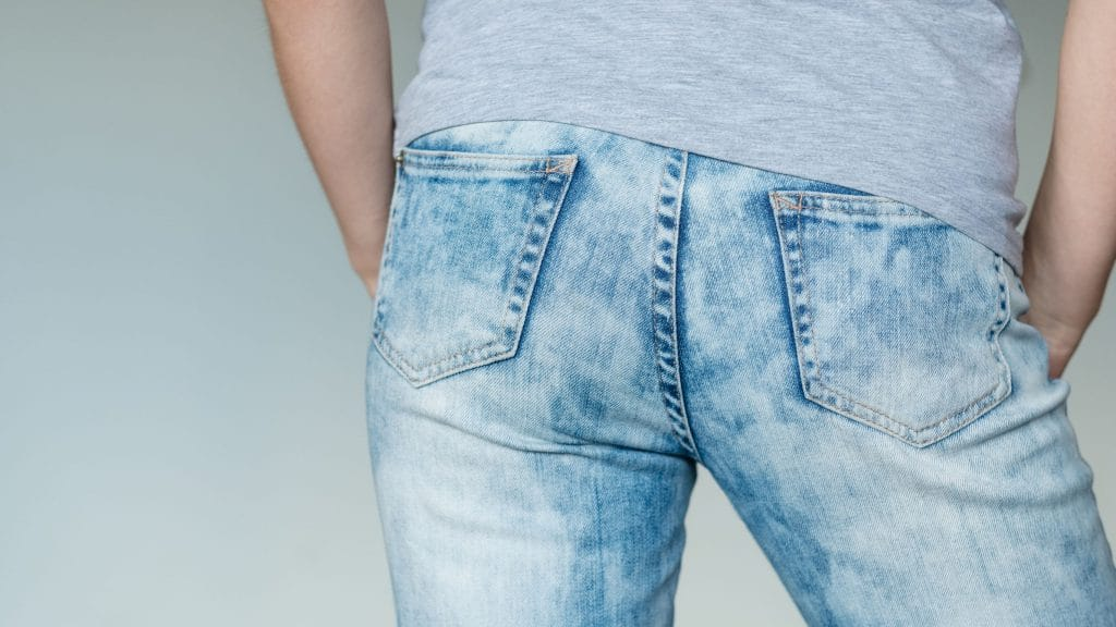 Homem de costas usando calça jeans e blusa branca. Foque na bunda dele.