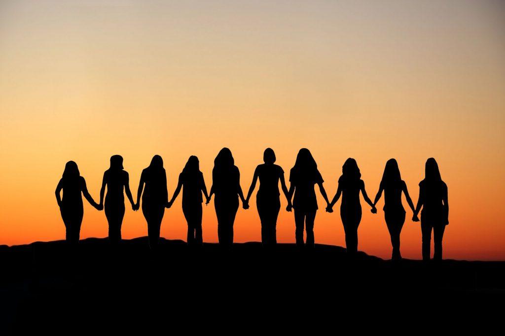 Silhueta de diversas mulheres de mãos dadas observando o pôr do sol.