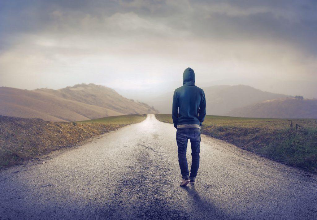 Homem vestindo calça jeans e blusa com capuz azul caminhando em uma estrada do interior, cercada de vegetações e montanhas